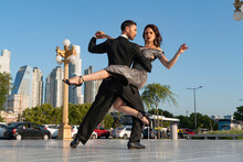 Confident Male And Female Dancers Practicing On Footpath Against Blue Sky