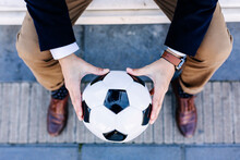 Businessman Holding Soccer Ball While Sitting On Bench