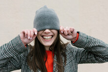 Smiling Woman Covering Eyes Through Knit Hat Against Wall