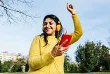 Smiling Woman With Mobile Phone Dancing While Listening Music Through Headphones Against Sky In Public Park