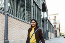 Smiling Woman Looking Away While Walking By Building