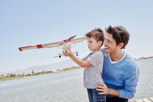 Boy Holding Airplane Toy While Standing By Father On Sunny Day