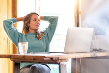 Female Freelancer With Hands Behind Head Relaxing At Home Office