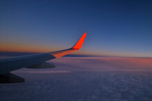 Wing Of Commercial Airplane Flying Against Sky At Dusk