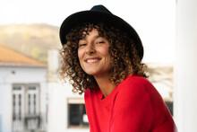 Curly Woman Wearing Hat In Balcony