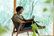 Young Man Using Digital Tablet While Sitting On Armchair By Window At Front Yard