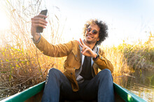 Young Man Gesturing Peace Sign While Taking Selfie Through Mobile Phone Sitting In Canoe On River