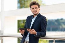 Mid Adult Businessman With Digital Tablet Looking Away While Leaning On Railing At Office Terrace