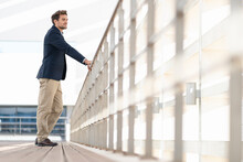 Businessman Looking Away While Standing By Railing At Office Terrace