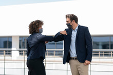 Colleagues Giving Elbow Bump While Greeting At Office Building Terrace