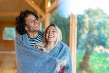 Happy Couple Covered In Blanket Smiling While Standing By Window At Front Yard