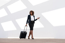 Businesswoman With Mobile Phone And Wheeled Luggage Walking Against White Wall