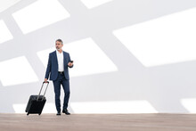 Male Entrepreneur Holding Mobile Phone While Walking With Luggage Against White Wall