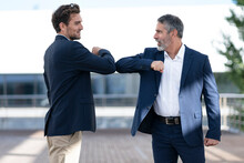 Entrepreneurs Greeting With Elbow Bumps While Standing At Office Terrace