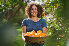 Smiling Curly Haired Woman Holding Basket Of Oranges While Standing In Garden