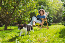 Happy Woman With Laptop Looking At Cat While Sitting On Deck Chair By Lemon Tree