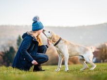 Young Woman In Knit Hat Playing With Dog In Field