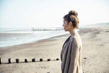 Young Woman Contemplating While Standing On Beach During Sunny Day