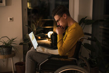 Concentrated Oung Man In Wheelchair With Laptop Working Late While Sitting On Wheelchair In Living Room