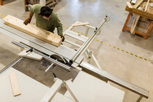Young Male Carpenter Working At Table Saw In Workshop