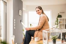 Female Entrepreneur With Laptop Sitting On Desk At Home