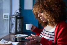 Young Woman With Coffee Cup Using Digital Tablet While Sitting At Cafe