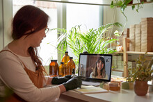 Female Entrepreneur On Video Call With Customer Through Laptop At Workshop