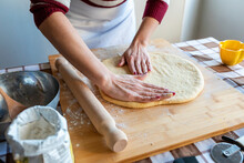 Woman Flattening Dough On Cutting Board With Hands To Make Croissants In Kitchen