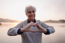 Smiling Man Making Heart Shape With Hands While Standing Against Lake