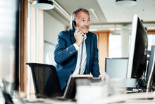 Smiling Businessman Looking Away While Talking On Telephone In Front Of Computer In Office