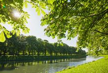Germany, North Rhine-Westphalia, Cologne, Sun Shining Over Treelined Decksteiner Weiher Pond In Spring