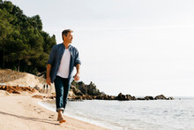 Mature Man Walking On Beach Against Clear Sky During Sunny Day