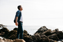 Enjoying Mature Man Standing Amidst Rock By Sea During Sunny Day