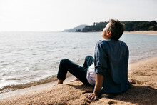 Relaxed Man Sitting On Shore At Beach During Sunny Day