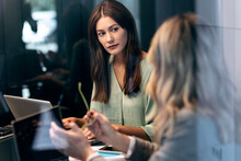 Businesswoman Having Discussion With Young Colleague While Sitting In Office