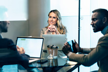 Smiling Businesswoman With Hand On Chin Listening To Businessman While Sitting In Meeting At Office