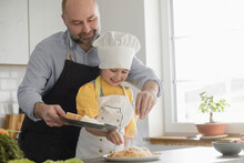 Smiling Father And Daughter Adding Seasoning While Standing In Kitchen At Home