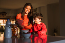 Happy Mother And Son Preparing Breakfast Together At Home