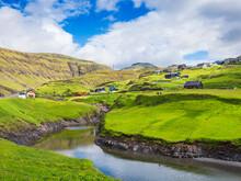 Houses Over Meadow In Leynar Village Against Sky, Iceland