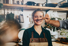 Chef Making Mustache Of Dry Chili To Colleague While Standing In Kitchen