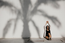 Young Woman With Arms Raised Sitting By Palm Tree Shadow On White Wall