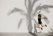 Young Woman Jumping With Arms Outstretched Against Shadow On White Wall