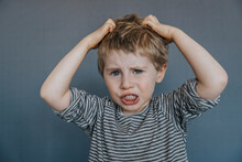 Frustrated Boy Scratching Head Against Gray Background
