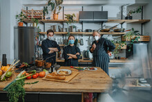 Confident Chef Wearing Protective Face Mask Staring While Standing At Kitchen