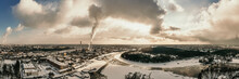 Germany, Berlin, Smoking Power Plant Chimney Towering Over Frozen Spree River