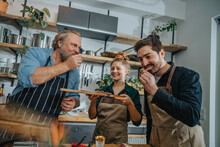 Male Chefs Tasting Salami While Standing By Colleague In Kitchen