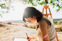 Young Woman Artist Drawing In Spiral Notebook While Sitting Next To Easel