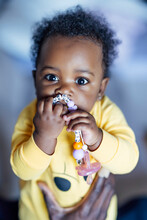 Baby Girl Chewing Toy While Held By Man