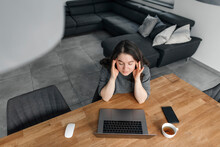 Tired Woman Sitting With Laptop At Table In Living Room