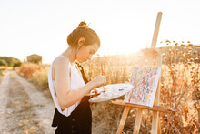 Young Woman Artist Painting On Easel